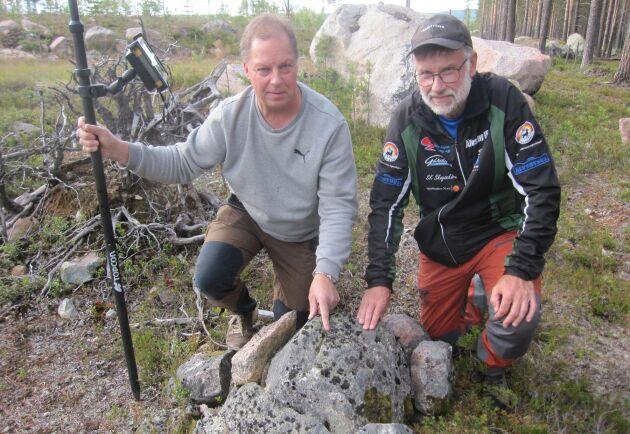 Robert Grimm, till vänster, och Roland Jansson, styrelseledamot Arvidsjaurs Allmänning, vid en råsten med huggen fyrkant markerar slutet på en rågång. Det här sättet att markera användes från slutet av 1800-talet till 1930-talet.