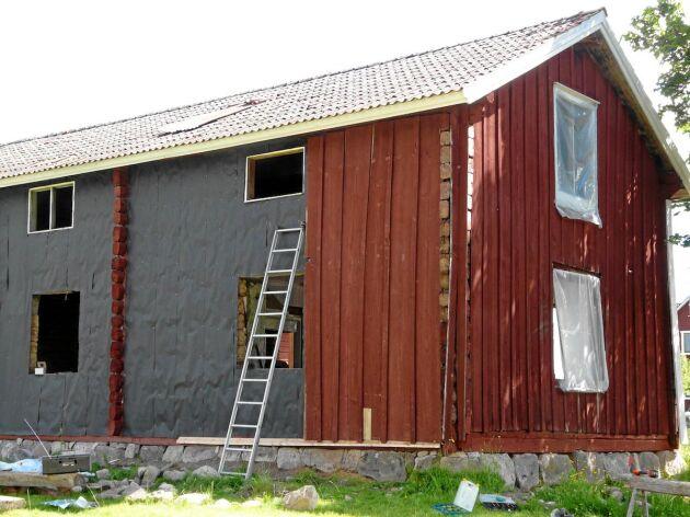 Ny isolering bakom de gamla brädorna på fasaden,.