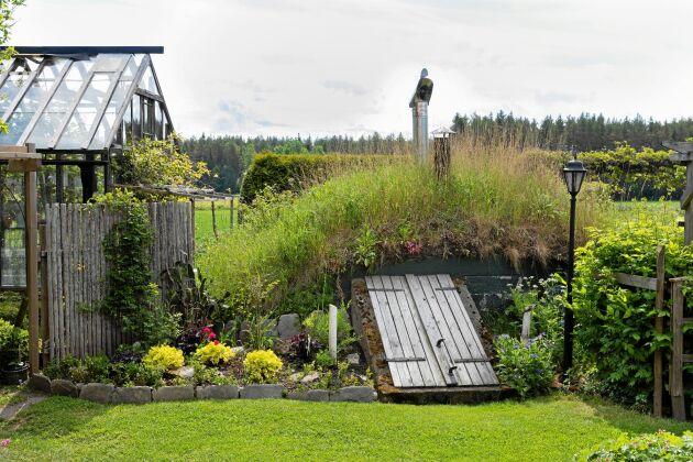 """En bakgård kan också vara vacker! Runt växthuset har Eva och Åke samlat praktiska funktioner som jordkällare, planteringsbord och """"barnkammare"""" åt växterna."""