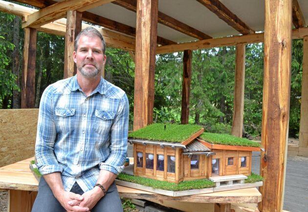 Erik Hjärtfors bredvid en modell av de stugor han timrar till en fritidsby på sin fastighet.