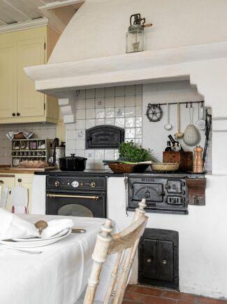 Vedspisen och den murade kåpan i köket ser ut att ha suttit där i minst hundra år.