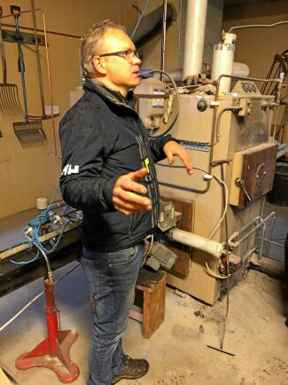 Magnus Axelsson demonstrerar hur flispannan han själv har byggt om producerar gratis värme till växthuset samtidigt som han får ut biokol som är mer värt än flisen han köper.