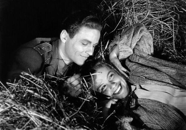 Kärlek på loftet. Sickan Carlsson fick ofta spela flirtande huvudroller i Svenska komedier. Sedermera gifte hon sig med gummikungen Nils Adamssons son. Här vänslas hon med George Fant i filmen Landstormens lilla argbigga från 1941.
