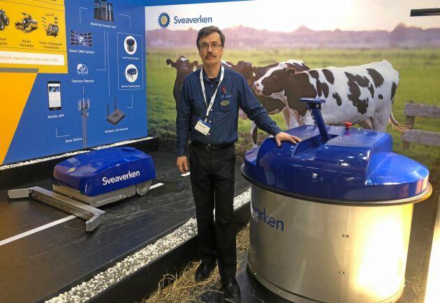 Jan Stendahl visar upp de nya robotarna, en foderputtare och en gödselskrapa.