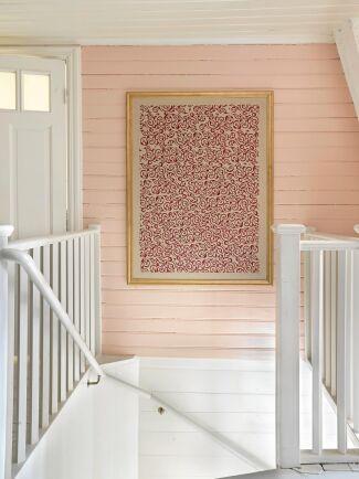 Ovanvåningens hall är färgsatt med ljus rosa väggar. Tavlan har Maria gjort.