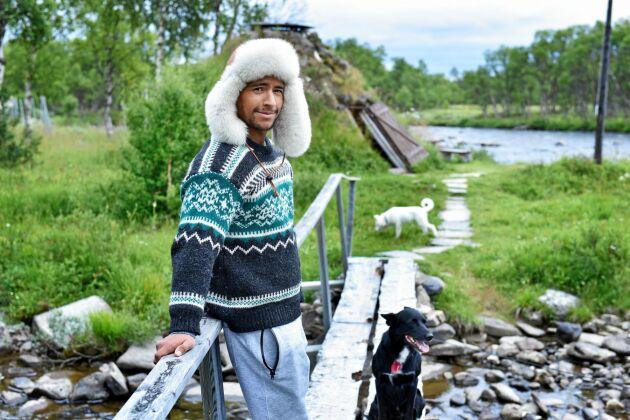 Jon Henrik står vid spången över till en bevarad, traditionell kåta i Mittådalens sameby.