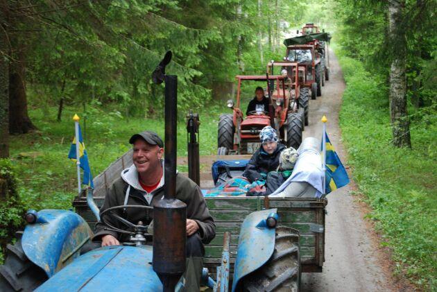 Fredrik Sundström, en av de ansvariga bakom traktorrallyt, med barnen på släp i kärran.