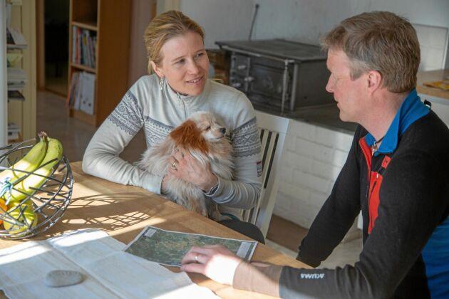 Evelina och Roger sitter med kartor i köket och planerar kommande jaktevenemang.