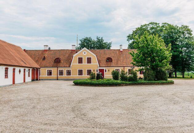 I den vitkalkade gårdsbyggnaden på totalt 300 kvadratmeter finns två lägenheter, dubbelgarage och häststall med 5 boxar.