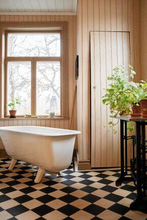 Badrummet med gammaldags badkar på tassar, rutigt golv och växter på piedestal.