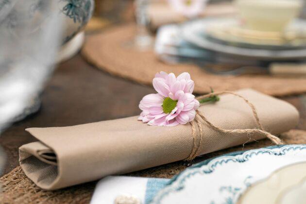 Det behöver inte kosta mycket för att det ska bli fint. En servett blir något alldeles extra med en blomma. Använd dig av det som finns i naturen. Foto: Pia Gyllin