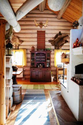 Rustik inredning med runda stockar i väggpanelen som pryds av renskinn, vilthorn och hemvävda textilier.