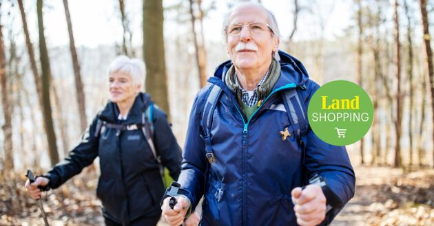 Retired senior man walking in front with a woman behind on a forest trail. Elderly people on a country walk.