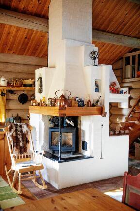 En stadig murstock går från golv till tak med två eldstäder som sprider skön värme.
