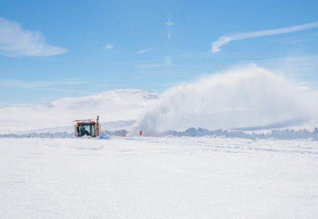 Snön sprutar upp ur den djupa skåran när Fjellströms Entreprenad röjer snön från vildmarksvägen.