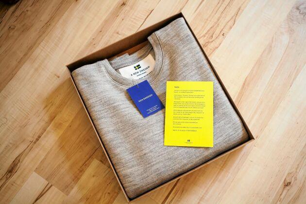 Lisa packar tröjorna i miljövänliga kartonger med ett litet tack-kort, där det står hur man bäst ska ta hand om plaggen.