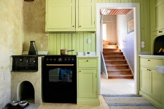 Den lindblomsgröna färgen i köket är samma nyans som originalfärgen från 1912. Vedspisen och hörnskåpet är från samma år.