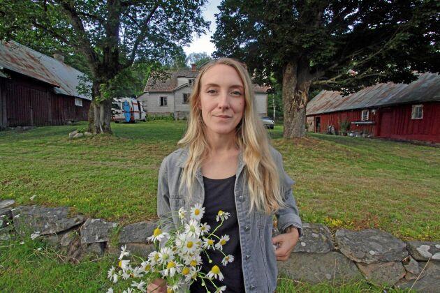 Emilia Lindholm framför sin ödegård med stort renoveringsbehov som hon köpte för 35000 kronor.