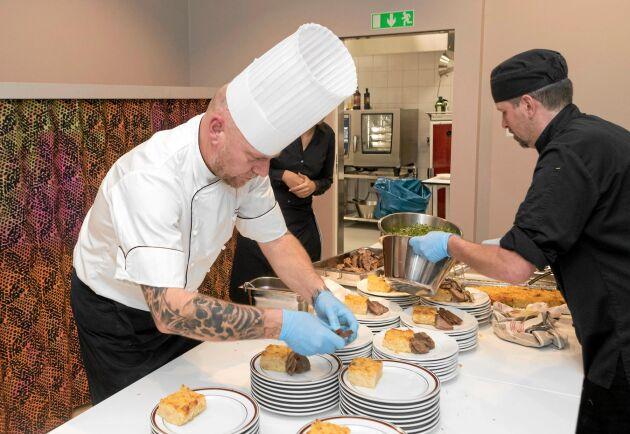 Kocken Arne Peterson och servispersonalen serverar huvudrätten vid invigningen. Vildsvin, lokalt skjutna, stod på menyn.