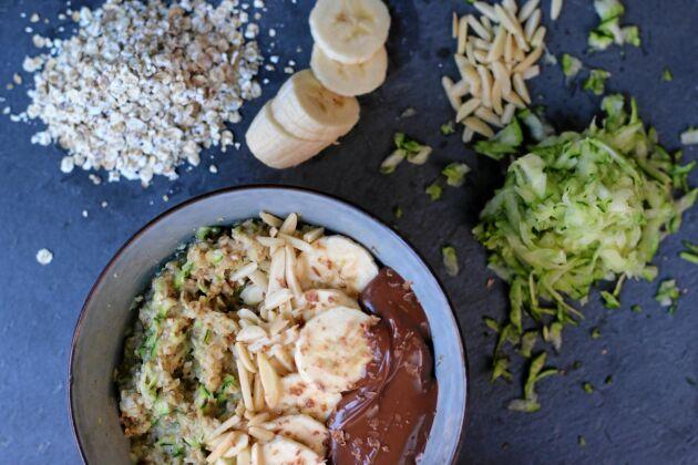 Zoats är en gröt med riven zucchini i. Här är den toppad med skivad banan, hackade mandlar och hasselnötssmör.