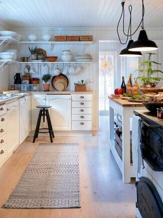 Ett luftigt kök med pärlspont, ljusa färger och hyllor i stället för överskåp.