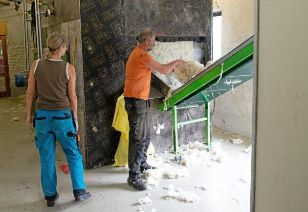 När ullen tvättats i fem olika kar går den genom sköljen och vidare på ett transportband in i torken. Jenny Andersson och Hans Bulthuis ser till att det som hamnar på golvet kommer med på bandet.