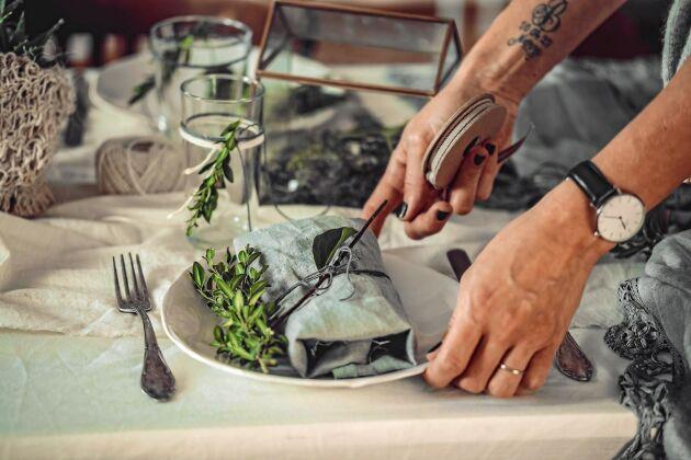Skrynkligt linne i lager på lager på bordet tillsammans med gamla silverbestick och en slarvigt hopknuten linneservett.