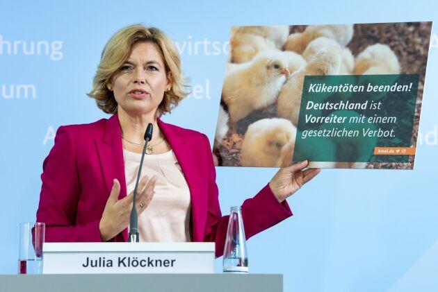 """Tysklands jordbruksminister Julia Klöckner (CDU), på en presskonferens där förslaget presenterades. På skylten står det """"Sätt stopp för tuppkycklingsdödande! Tyskland är föregångsland med ett förbud i lagen""""."""