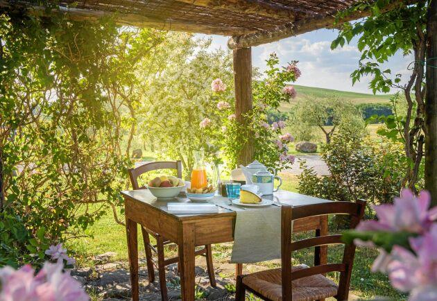 Stockbygge med golv av natursten. Pergolan bjuder på den perfekta frukostplatsen.