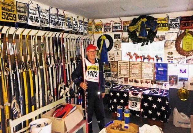 Börje Karlsson bland skidor och startnummer som han haft i Vasaloppet genom åren.