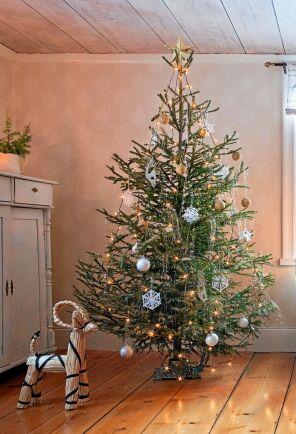 Gnistrande vacker gran med julkulor i guld och silver och virkade snöflingor.