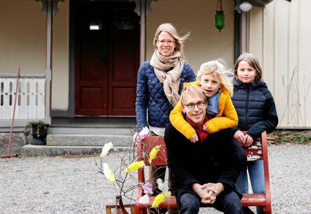 Familjen Lindgren, mamma Jenny, pappa Johan och barnen Sigrid och Valter vid sin utemöbel en gammal kyrkbänk.