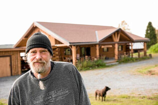 """Dick Bewarp framför sin """"Cowboykåk"""" som han timrat själv i jämtländska Mårdsjön. Huset är på totalt 256 kvadratmeter med härligt, öppen planlösning."""