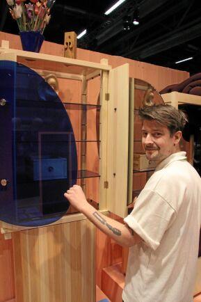 Snickarstudenten Oscar Wall på Carl Malmstensskolan visar furuskåpet Amorfo med utbytbara luckor, här i blått glas och spegelglas.