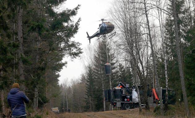 Helikoptern byter spridarbehållare i stort sett i farten.