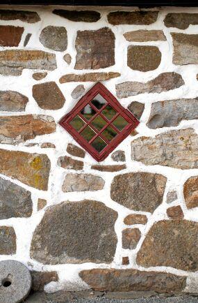Logens väggar är rejäla, murade i natursten med vackra detaljer av spröjsade fönster.