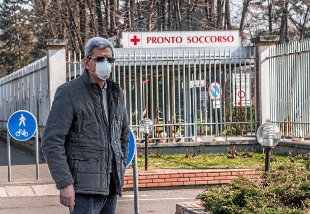 En man med mask utanför akutmottagningen i Italienska Codogno som stängt på grund av coronaviruset Covid-19.