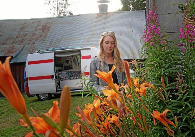 Emilia framför husbilen, som inretts med säng och möbler.
