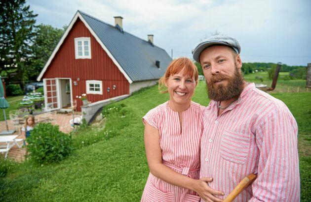 Stolta bakstuesittare Lella och David Ernstedt framför sitt hus med de tillbyggda köksdelen närmast där skafferiet ligger mot backen och därför svalt.