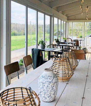 På charmig udda stolar kan gäster sitta och se ut genom de stora fönstren över grusvägen.