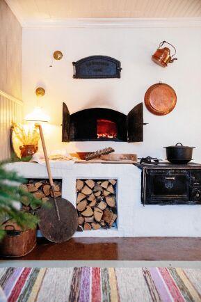 Den rejäla bakugnen och murstocken sprider värmen i huset. Joar har murat bänken med plats för ved.