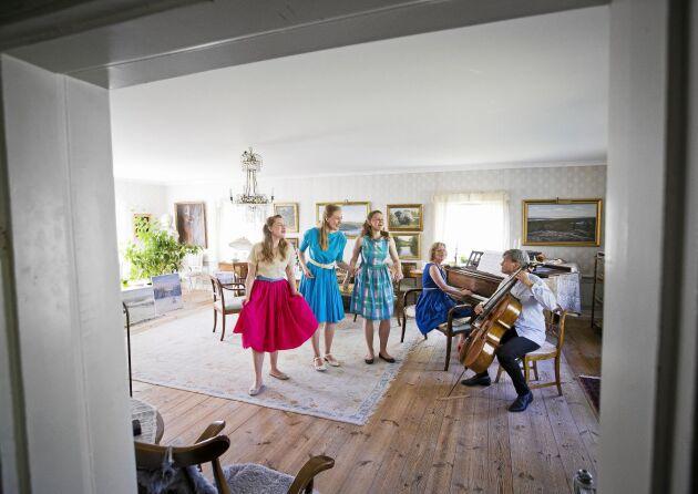 Spontan familjekonsert i salongen: Maria, Emelie och Josefine sjunger och stampar takten medan mamma Ulrika spelar piano och pappa Lars-Inge cello.
