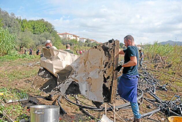 Frivilliga jobbar för att rensa upp efter flodvågens förstörelse.
