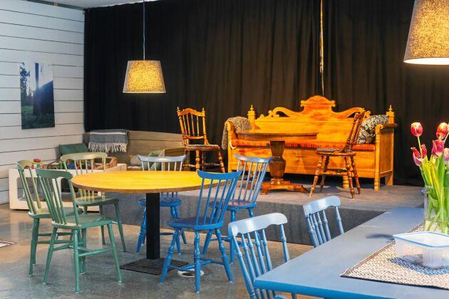Kökssoffa och färgglada pinnstolar i den del av restaurangen där det finns en scen med plats för artister.