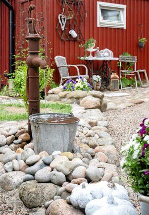 Kreativt återbruk har förvandlat en rostig pump och en gammal hink till ett vattenspel som porlar rofyllt. Fint inramat med lösa, runda stenar.