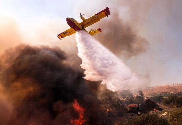 Ett flygplan vattenbombar en skogsbrand i Simi Valley, Kalifornien, i novmeber 2018.