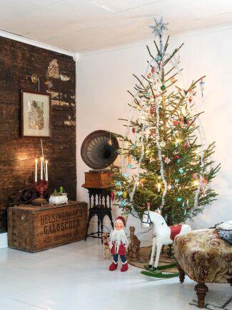 Charmig julgran som man gärna tar en närmare titt på. Förutom glitter och svenska flaggor finns också julgranskulor, kottar, papperspyssel och små strutar.