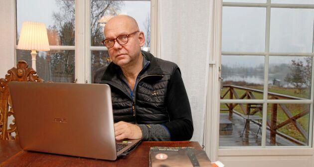 Mikael Näslund vid köksbordet med sin dator i släktgården. Storsjön i bakgrunden.