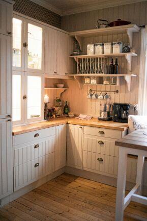 Köket är i gammaldags stil med pärlspont och vägghyllor.