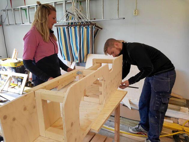 Jennifer och Robin lägger sista handen vid skåpet för diskbänken, utsågat i plywood.